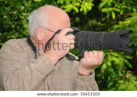 closeup image of senior using a long range zoom lens - stock photo