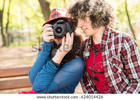 Closeup image of two young women in casual clothing talking and taking photos on a sunny day in nature. Sitting on bench in a city park and holding camera