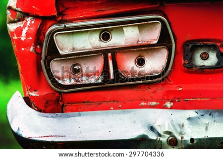 Closeup image of vintage rusty red car headlight at green background. - stock photo