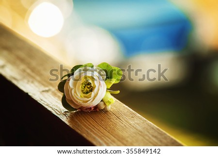 Closeup image of white rose boutonniere at natural outdoors background. - stock photo