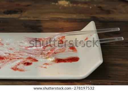 Closeup image white dish of white layer cake with strawberry jam topping. - stock photo
