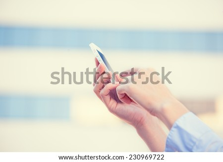 Closeup image woman hands holding using smart mobile phone isolated outside corporate building background. People new generation technology addiction concept. Customer service provider relationship - stock photo