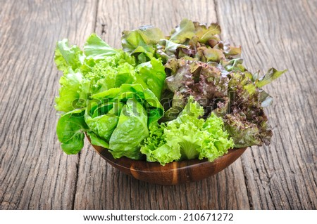 closeup isolate fresh lettuces in wooden bowl on wooden desk - stock photo