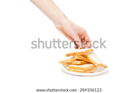 Closeup isolated shot of male hand taking piece of bread from plate - stock photo