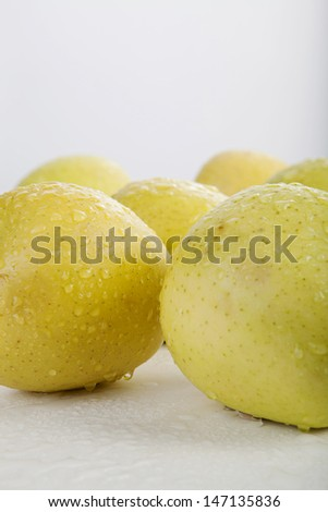 closeup isolated yellow apple with raindrop on white background