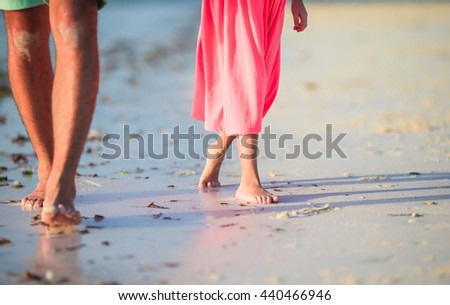 Closeup kid and adult feet on white sandy beach