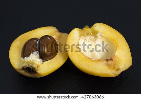 Closeup large ripe Eriobotrya japonica loquat fruit cut in half revealing shiny seeds on black background - stock photo