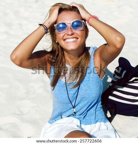 Closeup lifestyle fashion portrait of pretty young beautiful blonde smiling woman in blue sunglasses having fun outdoor in summer on vacation in windy sunny weather on the beach  - stock photo
