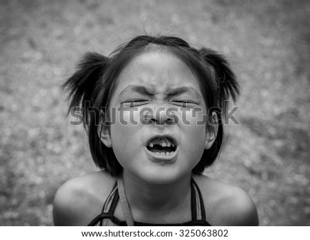 Closeup little asian girl with a broken teeth - stock photo