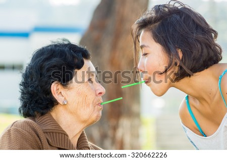 Closeup lovely hispanic grandmother and granddaughter enjoying quality time outdoors sharing snacks. - stock photo