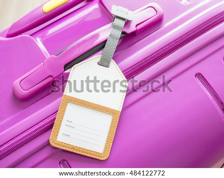 Closeup luggage tag on pink suitcase (Travel kit)