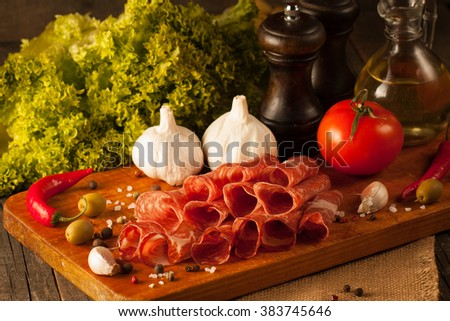 Closeup macro photo of thin slices of prosciutto with green olives, spices and food background on wooden cutting board. Raw dried meat.