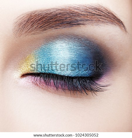Closeup macro shot of closed human female eye. Woman with natural evening vogue face beauty makeup. Girl with perfect skin and lilac - blue - yellow eyes shadows