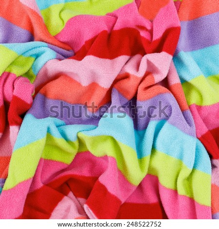 Closeup macro texture of colorful pink violet purple blue yellow green pink red fleece fabric, clothing background with wrinkles and folds - stock photo