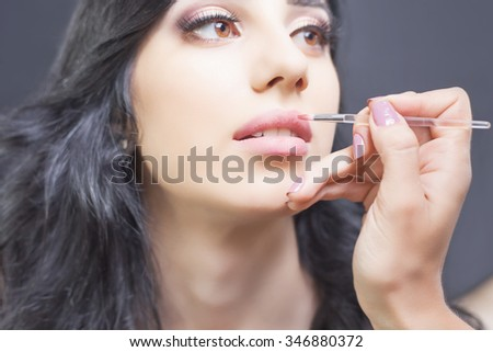 Closeup make up, specialist in beauty salon gets lipstick, lip gloss. Portrait of a Arabian woman. Beautiful professional make-up.