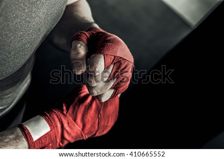 Closeup male hand of boxer with red boxing bandages. Fists of fighter before the fight or training in sport gym. - stock photo