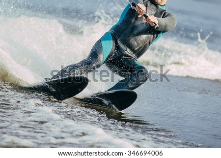 closeup man riding water skis on lake in summer. body parts without a face - stock photo