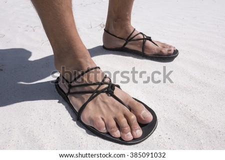 Closeup man's feet wearing primitive black sandals with string laces on white sand beach - stock photo