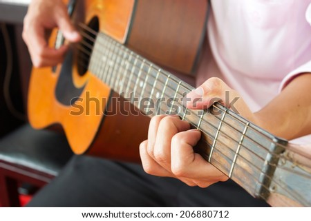 Closeup man's hands playing acoustic guitar with piano background. - stock photo