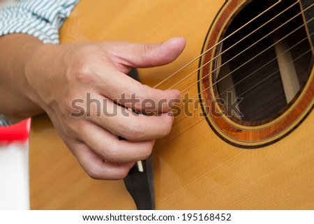 Closeup man's hands playing classic guitar.
