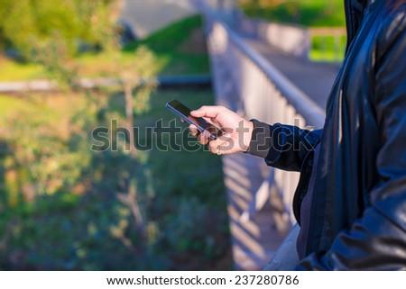 Closeup man's hands using mobile phone outdoors - stock photo