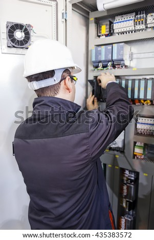 Closeup man worker checking advanced industrial control panel; note shallow depth of field