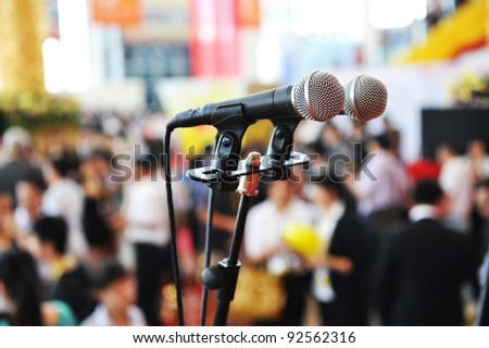 Closeup microphone in auditorium with people. - stock photo