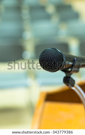 Closeup Microphone on the speech podium over the Abstract blurred photo of conference hall or seminar room background - stock photo