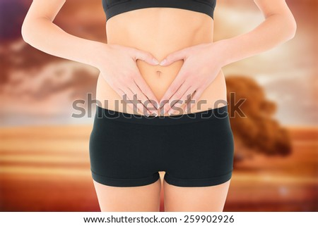 Closeup mid section of a fit woman in black shorts against sunrise over field with tree - stock photo