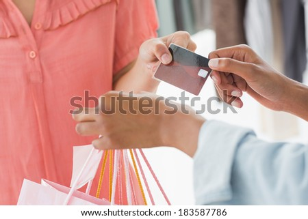Closeup mid section of female customer receiving shopping bags and credit card from saleswoman in boutique - stock photo