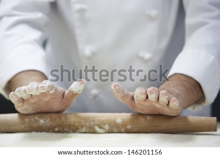 Closeup midsection of a chef rolling dough with rollingpin