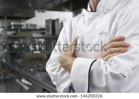 Closeup midsection of a male chef with arms crossed in kitchen