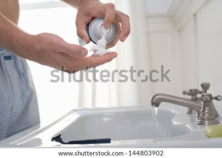 Closeup midsection of a man preparing to shave at bathroom sink - stock photo