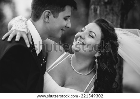 Closeup monochrome portrait of bride and groom embracing and laughing at windy day - stock photo