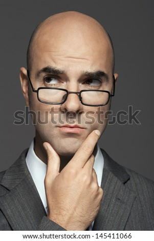 Closeup of a bald businessman wearing glasses with hand on chin against gray background - stock photo