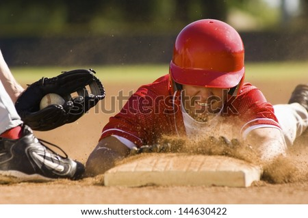 Closeup of a baseball player sliding to the base - stock photo