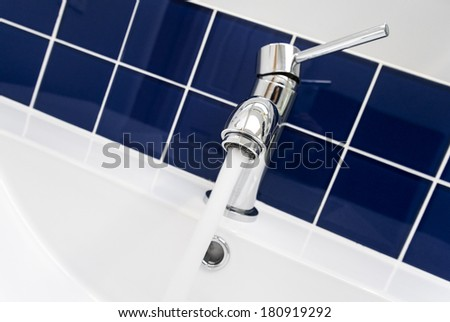 Closeup of a Bathroom Faucet With Blue Tiles as Background - stock photo