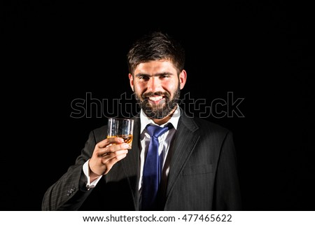 Closeup of a bearded business man smiling and holding a glass of whiskey