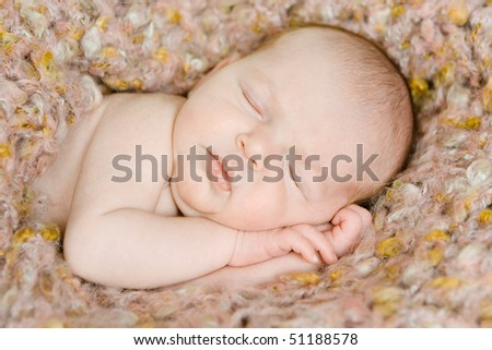 closeup of a beautiful newborn baby wrapped in a blanket sleeping - stock photo