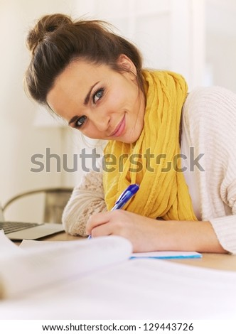 Closeup of a beautiful smiling woman looking at camera while writing on her notepad - stock photo