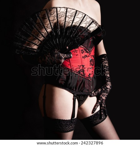 Closeup of a beautiful woman in erotic lingerie in front of black studio background - stock photo