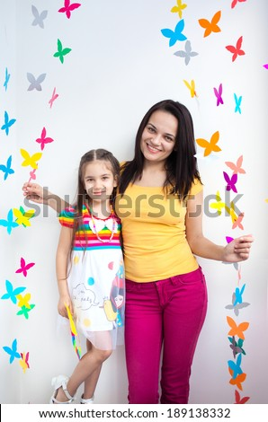 Closeup of a beautiful woman mother and her cute daughter kid child smiling and posing on a bright background of paper butterflies - stock photo