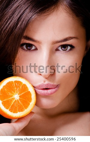 closeup of a beautiful woman`s face with orange - stock photo