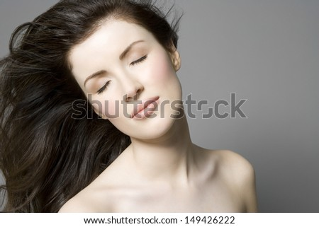 Closeup of a beautiful woman with long brown hair and eyes closed against gray background - stock photo