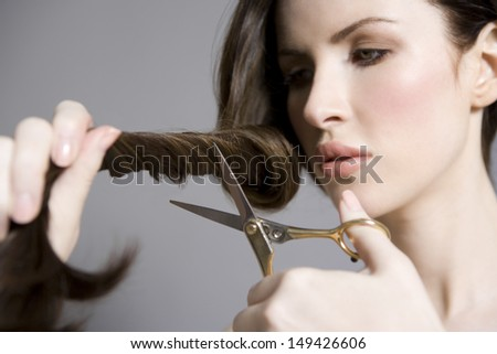 Closeup of a beautiful young woman cutting her long hair against gray background - stock photo