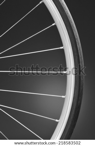 Closeup of a bicycle wheel on a light to dark black and white background. Only part of the wheel is shown. Vertical format with copy space.
