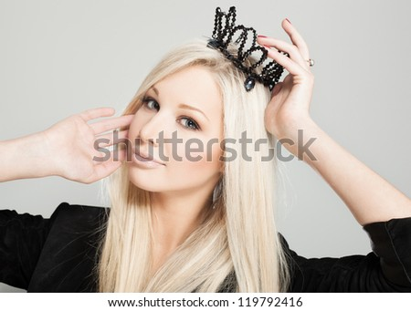 Closeup of a blonde woman with black crown, indoors - stock photo