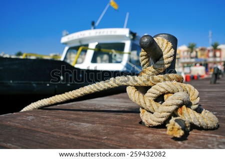 closeup of a boat tied with a rope on a mooring - stock photo