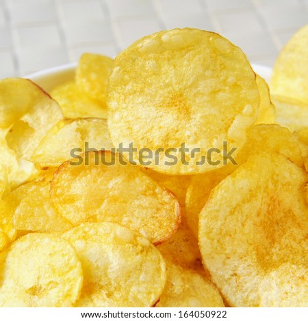 closeup of a bowl with appetizing potato chips - stock photo