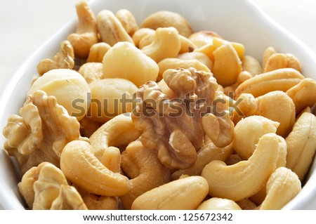 closeup of a bowl with mixed nuts, such as walnuts, macadamia nuts or cashews - stock photo